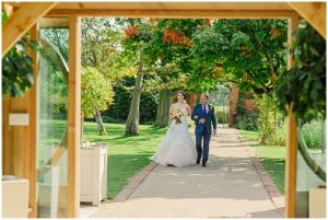 A bride is walked down the aisle to the Orangery for the wedding ceremony - autumn wedding