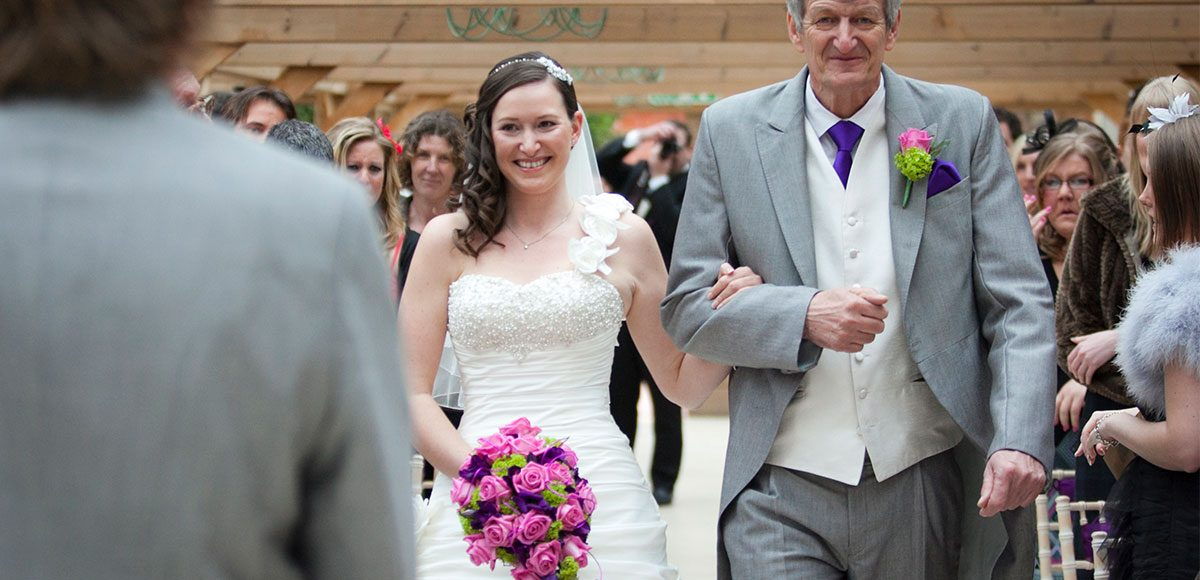 Bride walking down the aisle to the groom – wedding venues in Essex