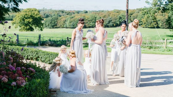 Bridesmaids stand together in the grounds of this countryside wedding venue with accommodation