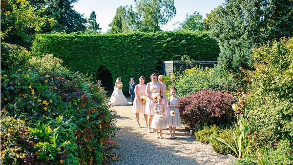 A bride and her bridesmaids walk along the Long Walk and through the Walled Garden - autumn wedding