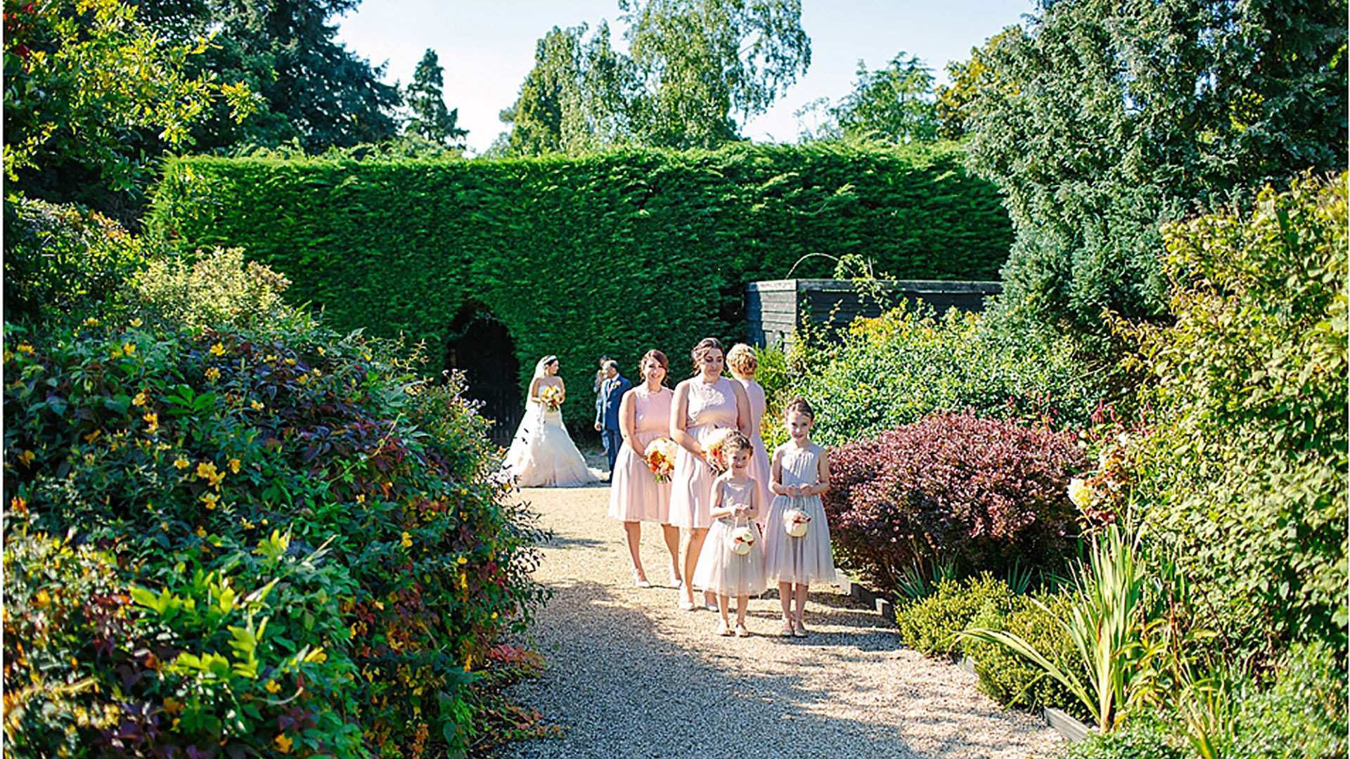 A bride and her bridesmaids walk along the Long Walk and through the Walled Garden - autumn wedding