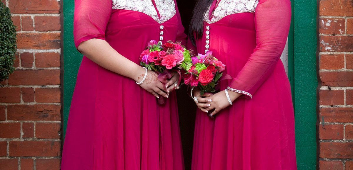 Bright pink bridesmaids dresses and flowers ready for a wedding ceremony