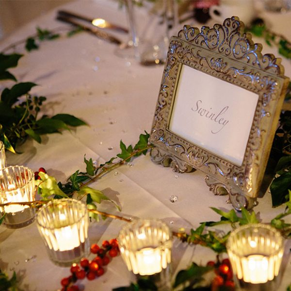 Table name with candles and holly.