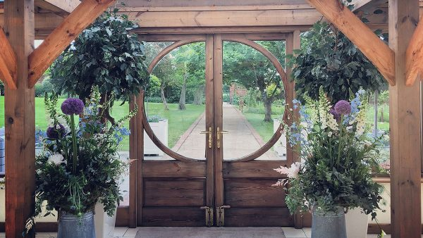 The Walled Garden can be seen through the oak door and glass windows of the Orangery - decorated here with purple flowers