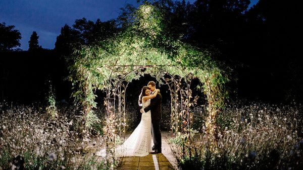 A happy couple embrace as they stand under the romantic wrought-iron pavilion at night - wedding photo ideas