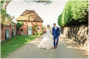 A happy couple hold hands with the charming Apple Loft Cottage in the background - honeymoon cottage
