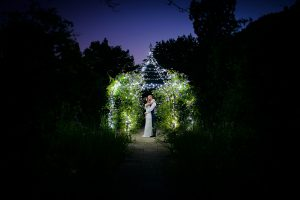 A bride and groom steal a moment under the wrought-iron pavilion at night - outdoor weddings