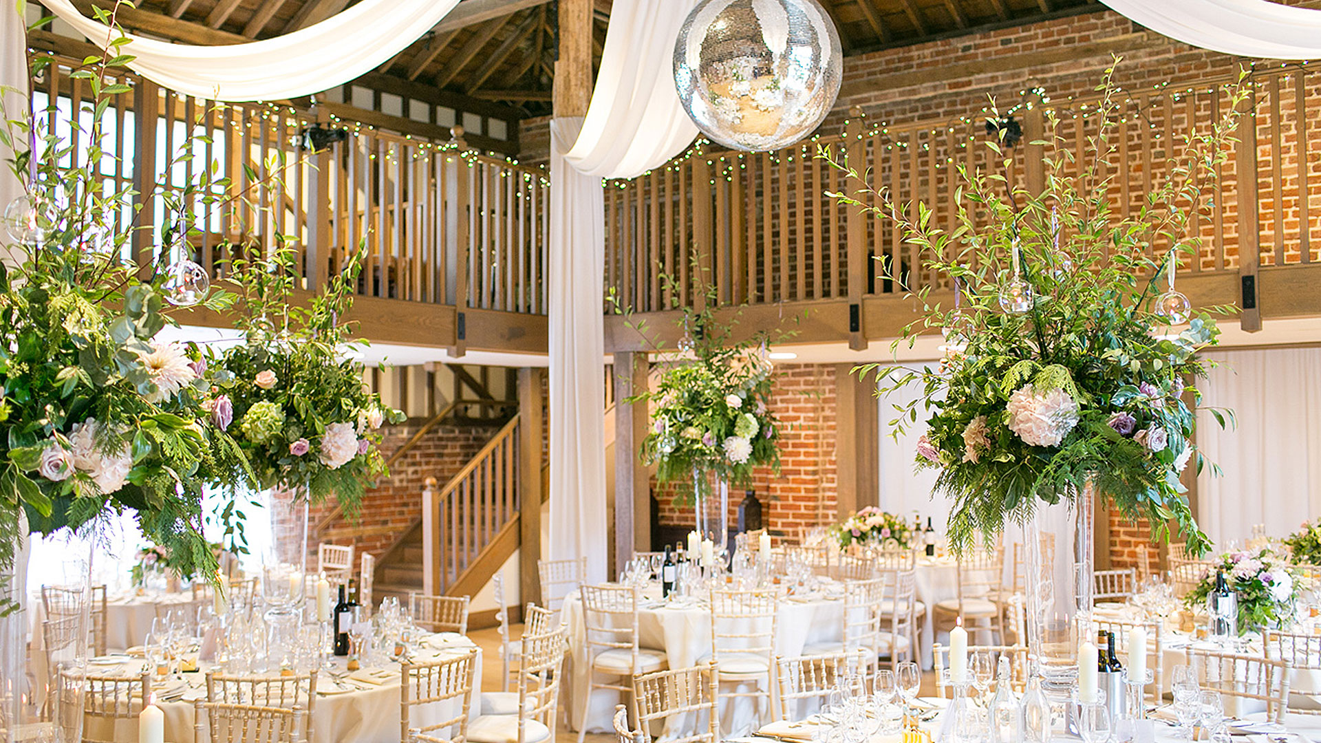 The Mill Barn is decorated with huge flower wedding table centerpieces and drapes from the ceiling