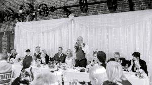 Wedding speeches are enjoyed by family and friends in the wedding barn