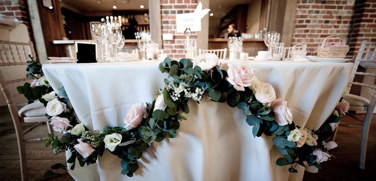 Floral garland used to decorate the tables in the Mill Barn – barn wedding Essex