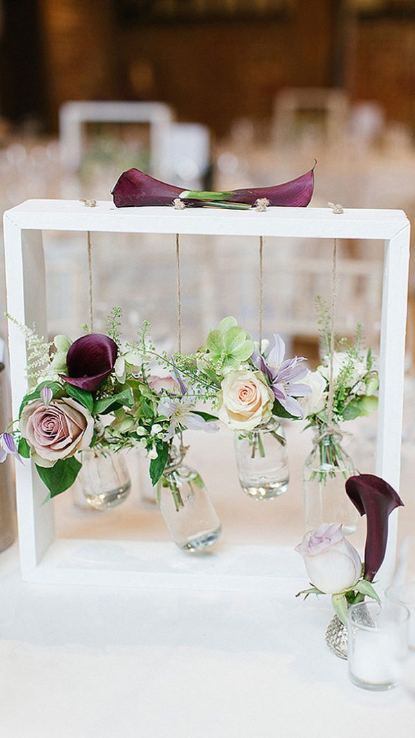 Pink and purple flowers hang in small glass jars as table centrepieces at this pretty summer wedding