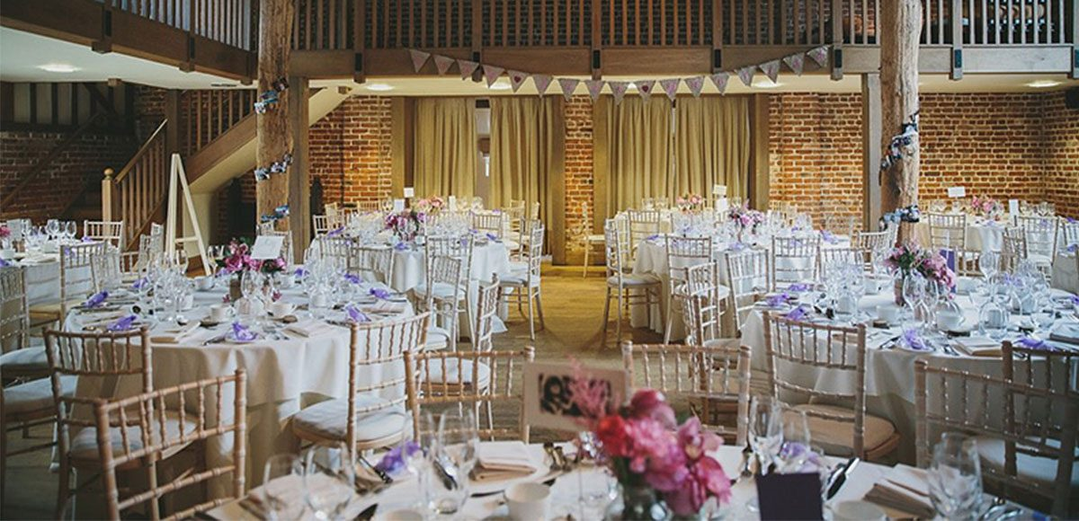 Dusky fall coloured floral centrepieces decorate the tables at this Gaynes Park wedding reception