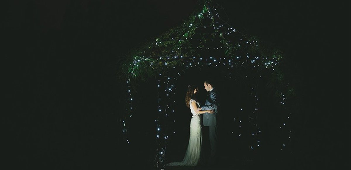 The happy couple stealing a previous moment under the pavilions twinkly fairy lights in the evening at Gaynes Park