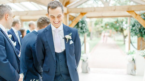 A smiling groom awaits the arrival of his bride in the Orangery - wedding ceremony venues Essex