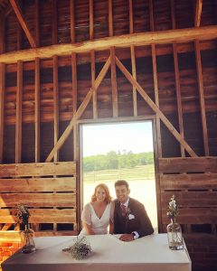 A happy couple sit and the wedding ceremony table in the Gather Barn - wedding barns Essex