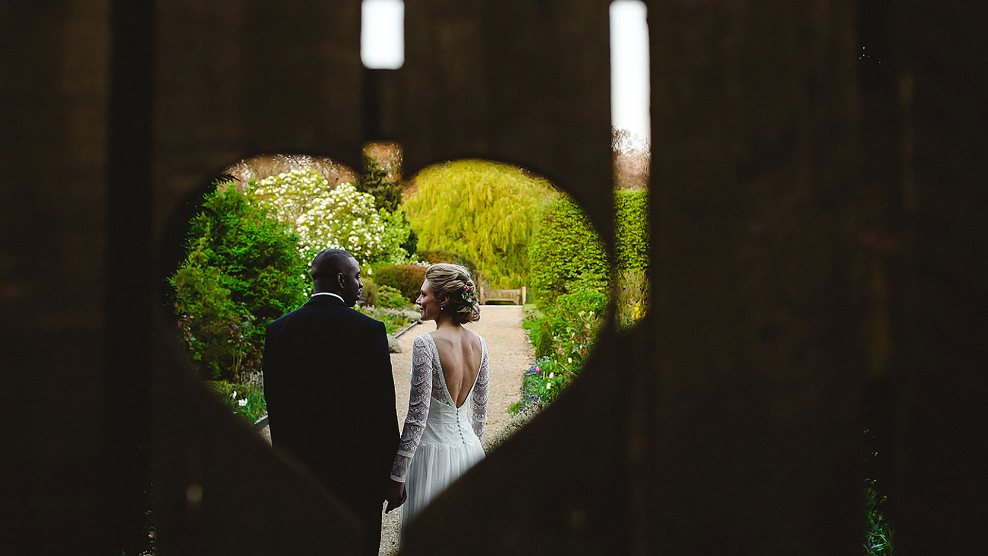 A bride and groom steal a moment behind the heart gate - wedding photos