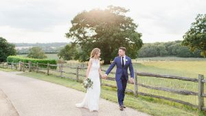 A happy couple hold hands during a stroll around this unique countryside wedding venue