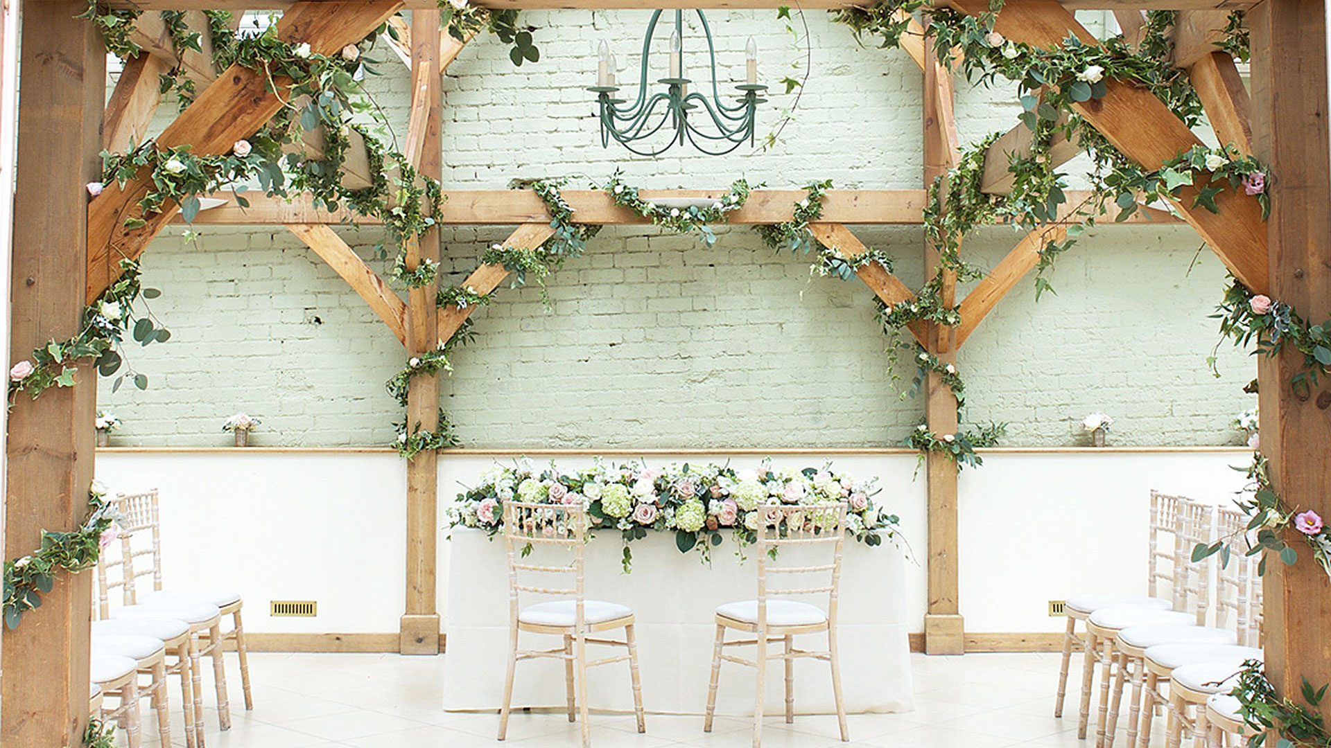 Ivy entwined with white roses is wrapped around the exposed oak beams inside the wedding ceremony Orangery
