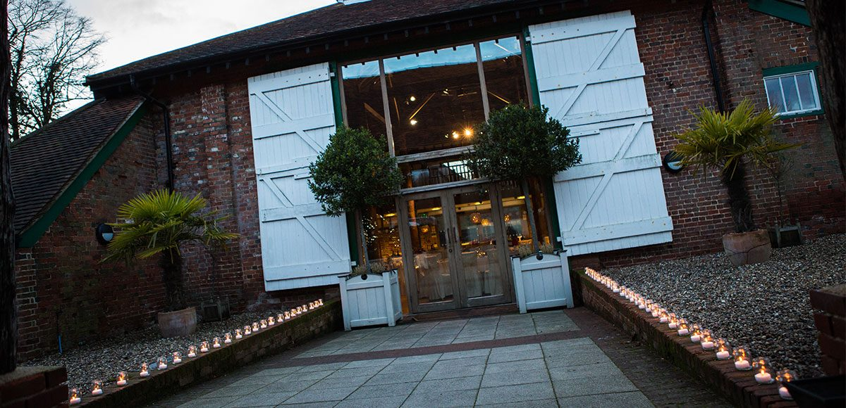 The Mill Barn at Gaynes Park surrounded by candles – wedding barns in Essex