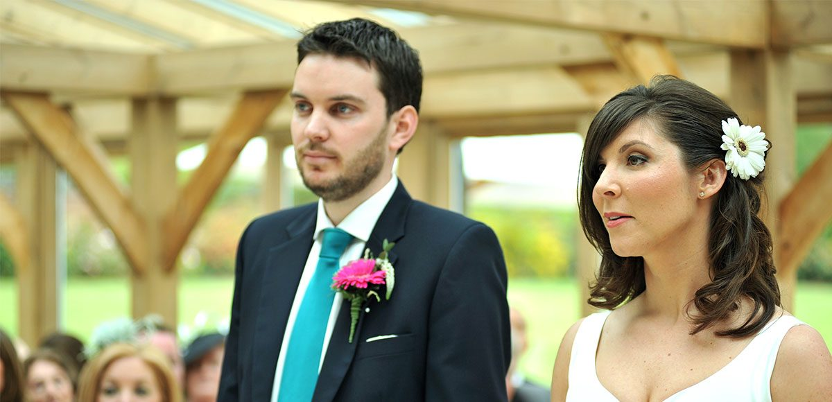 Bride and groom during their ceremony in the Orangery at Gaynes Park wedding venue