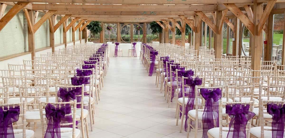 Orangery dressed with purple bows for a wedding ceremony