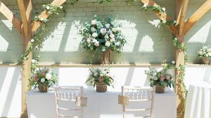 Pale pink and white roses decorate the wedding ceremony table in hessian baskets - rustic wedding ideas