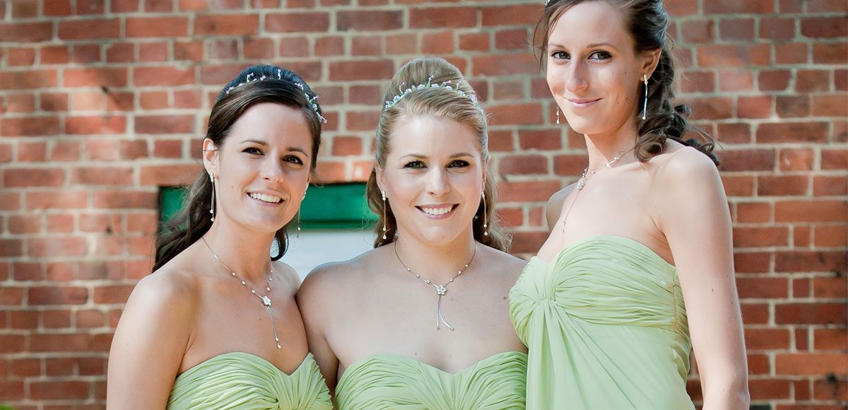 Bridesmaids in pastel green dresses ready for the ceremony at Gaynes Park