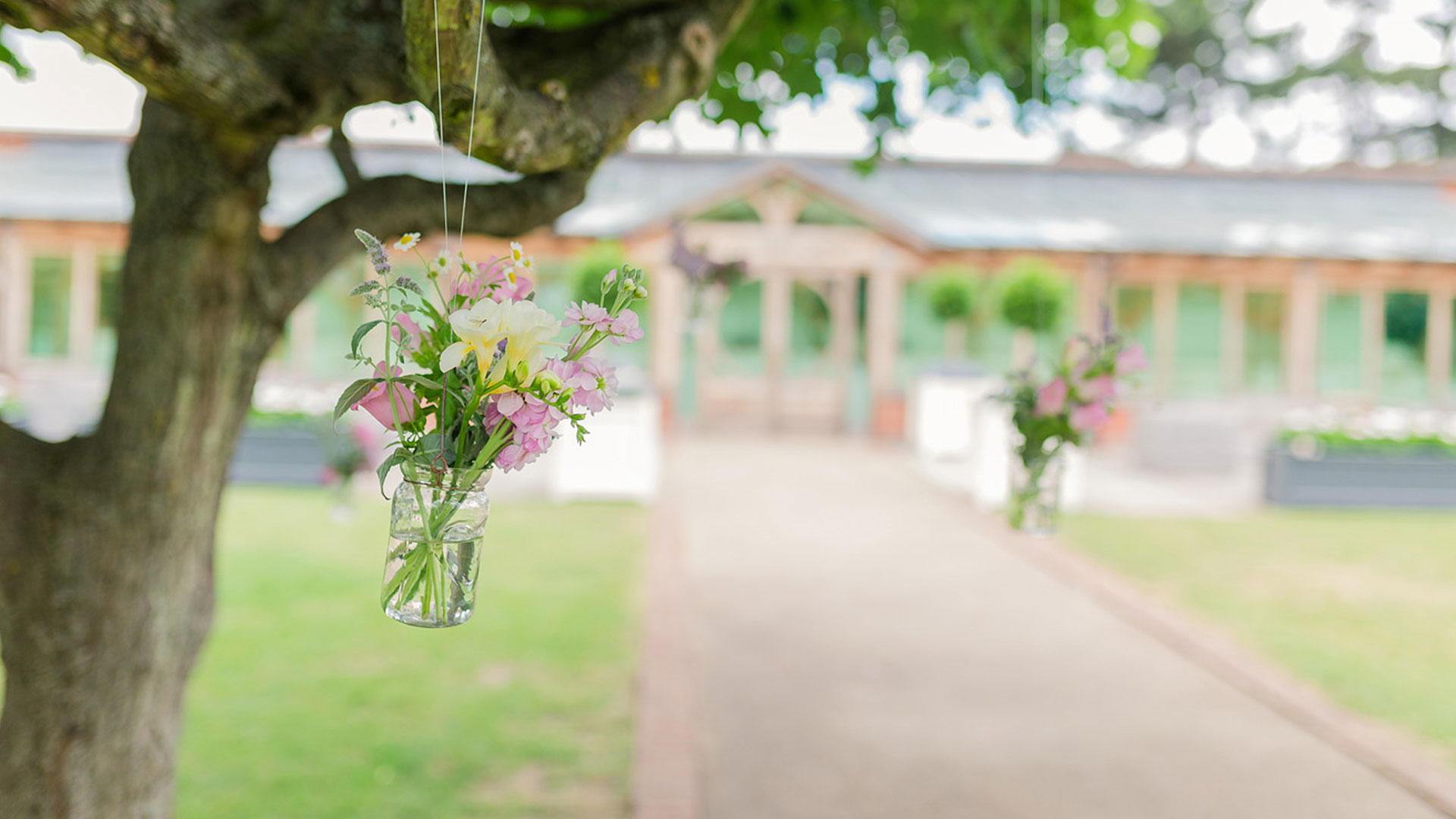 Hanging wedding flowers in clear glass jars from the trees in the Walled Garden is a gorgeous idea for a spring wedding