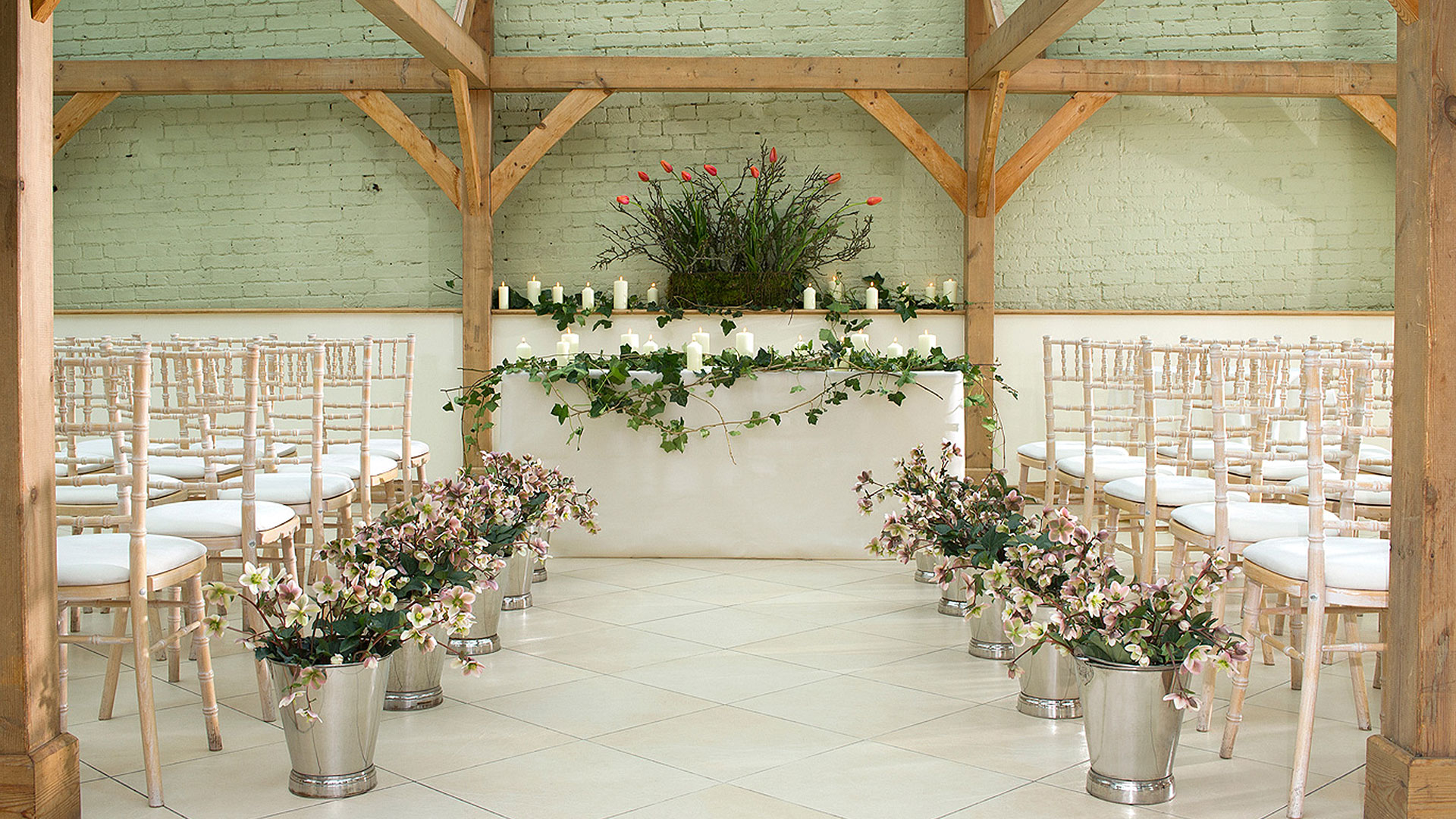 Beautiful pink flowers in silver planters line the wedding aisle at this stunning wedding ceremony barn