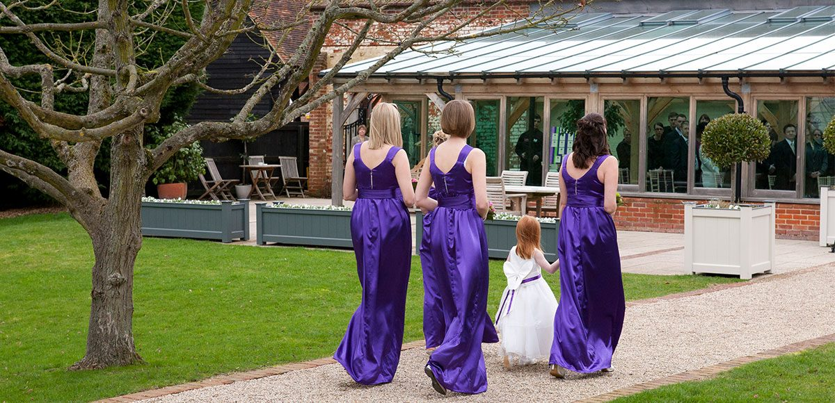 Bridesmaids wearing purple dresses walking down the Long Walk