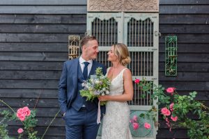 A couple stand between rose bushes for a picture perfect moment - rustic wedding