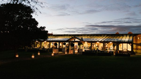 The Orangery looks beautiful at night and the wedding aisle lined with lanterns - ceremony wedding venues in Essex