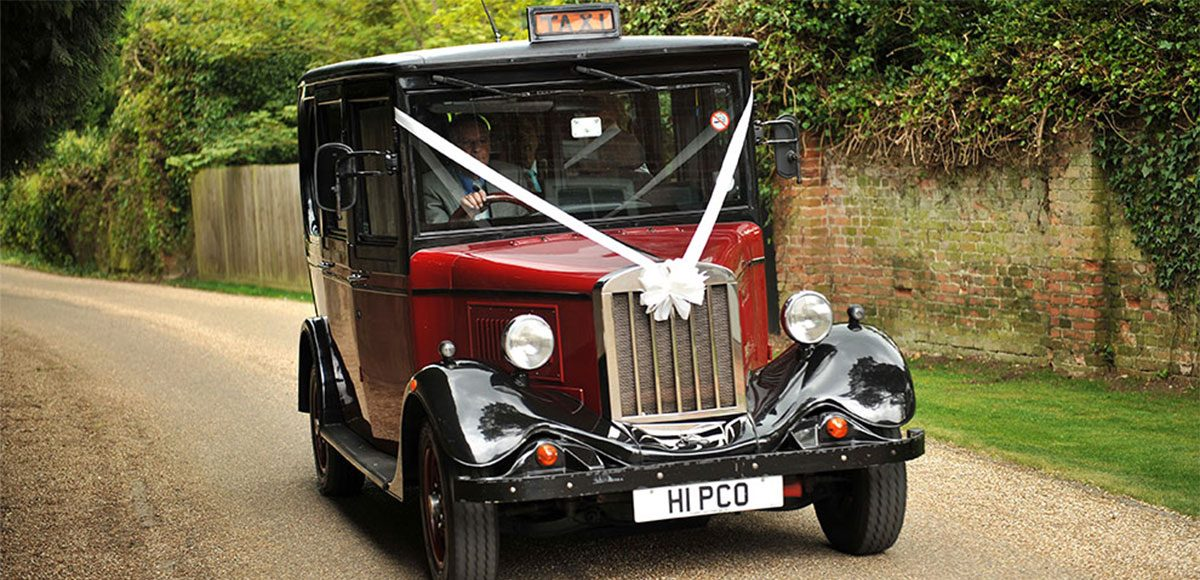 Arriving in style in their vintage wedding taxi