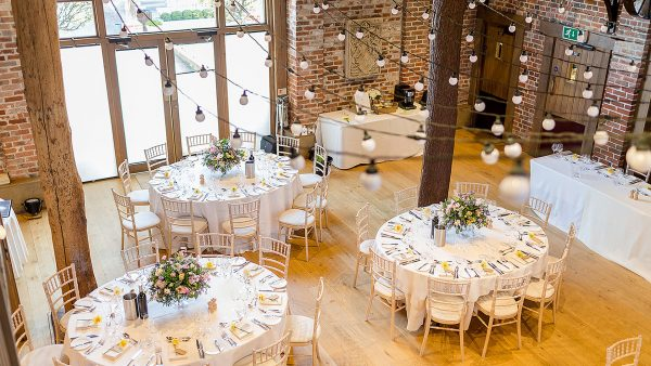 The Mill Barn is set up for a wedding with beautiful yellow and pink flowers for the table centrepieces