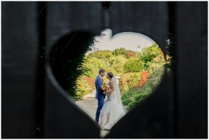 Couple share a moment behind the heart gate at Gaynes Park for a romantic wedding photo