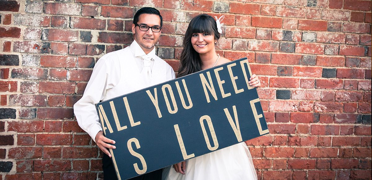 The happy wedding couple holding an all you need is love wedding sign