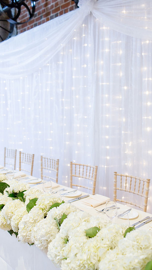 A white curtain with fairy lights hangs behind the top table inside Essex wedding barn