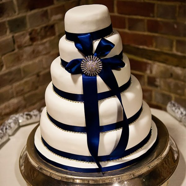 White cake with blue ribbon for a winter barn wedding reception.
