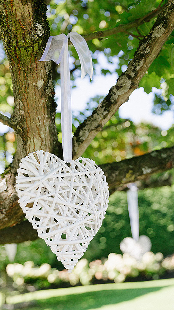 White wicker wedding hearts hung from trees add a pretty touch to your garden wedding - wedding ideas