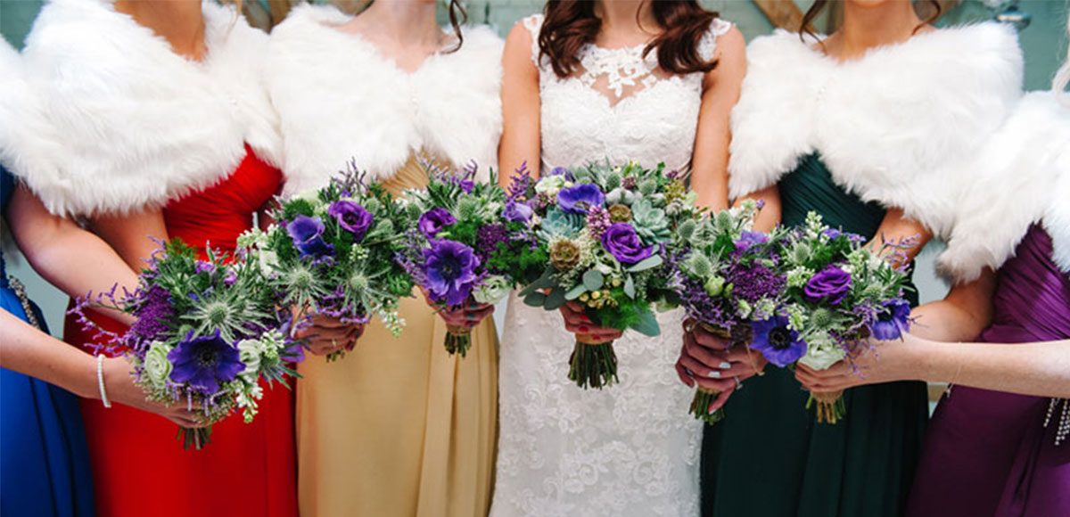 Bridesmaids wearing jewel tone dresses and white fur shawls for a wedding at Gaynes Park.