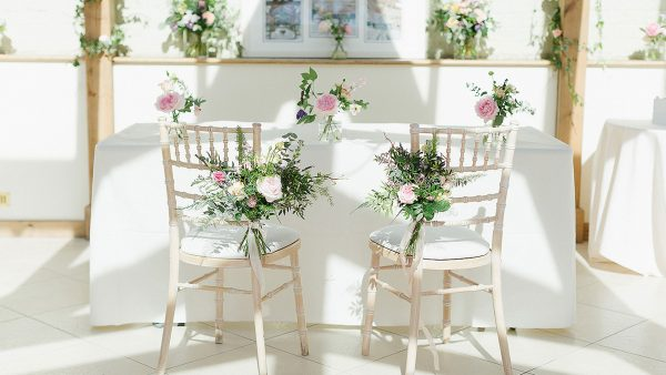 Flowers adorn wooden chairs at this pretty summer wedding at Gaynes Park wedding venue in Esssex