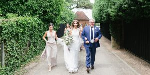A bride and her father make their way to the Long Walk leading to the stunning wedding orangery