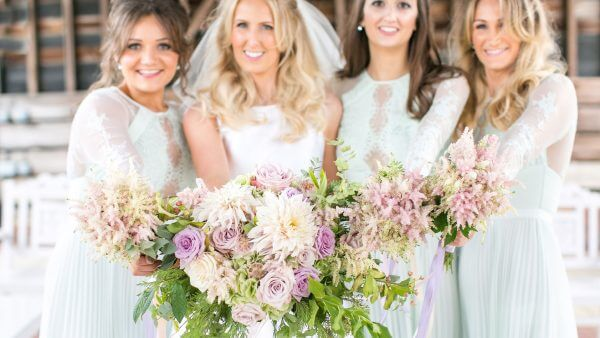A bride and her bridesmaids stand in the Gather Barn holding their pale purple flowers - wedding ideas