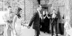 A bride and groom arrive into the Mill Barn for their wedding reception after their ceremony wedding at Gaynes Park