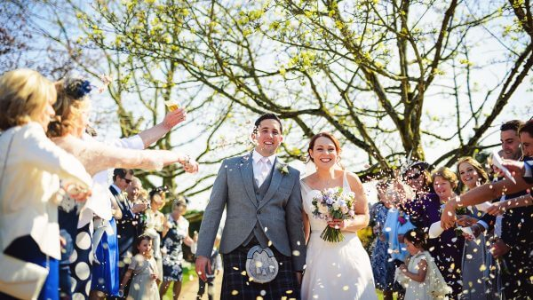 A bride and groom are congratulated with confetti after their wedding ceremony