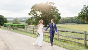 A happy couple stroll hand in hand as they enjoy the wonderful setting of this Essex wedding venue