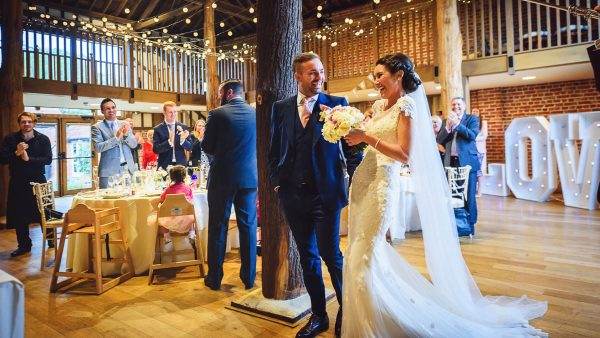 A bride and groom are welcomed into the stunning Mill Barn where they will hold their wedding reception