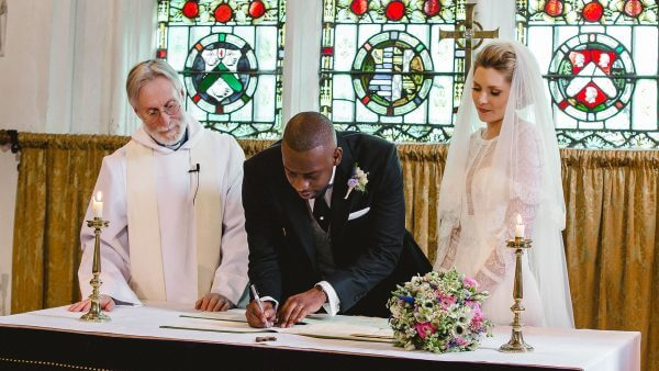 A bride and groom sign the register after saying their marriage vows - church wedding
