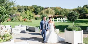 A bride and groom walk around the Walled Garden decorated with light-up letters - garden wedding ideas