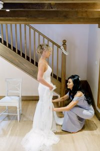 After applying finishing touches to her wedding hair and makeup a bridesmaid helps a bride into her wedding dress